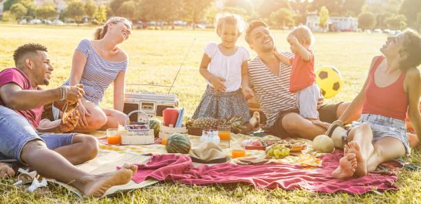 glückliche familien machen picknick im stadtpark - junge eltern spaß mit ihren kindern im sommer essen, tranken und lachten zusammen - liebe und chlidood konzept - schwerpunkt auf linken mann gesicht - mensch isst gras stock-fotos und bilder