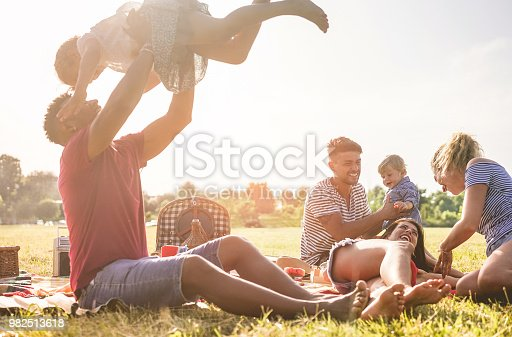 Happy families doing picnic in nature park outdoor - Young parents having fun with children in summer time laughing together - Positive mood and food concept - Main focus on right man face