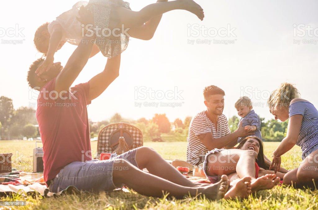 Glückliche Familien machen Picknick im Naturpark outdoor - junge Eltern Spaß mit Kindern im Sommer gemeinsam lachen - Positive Stimmung und Food Konzept - Schwerpunkt auf richtige Mann Gesicht – Foto