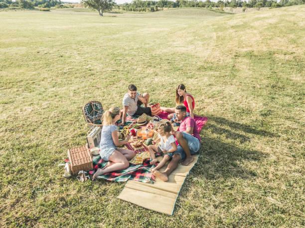 fröhliche familien beim picknick im park im freien-junge eltern, die im sommer spaß mit kindern haben, essen und spielen-essen, wochenendleben und freundschaftskonzept-schwerpunkt auf blondes mädchengesicht - mensch isst gras stock-fotos und bilder