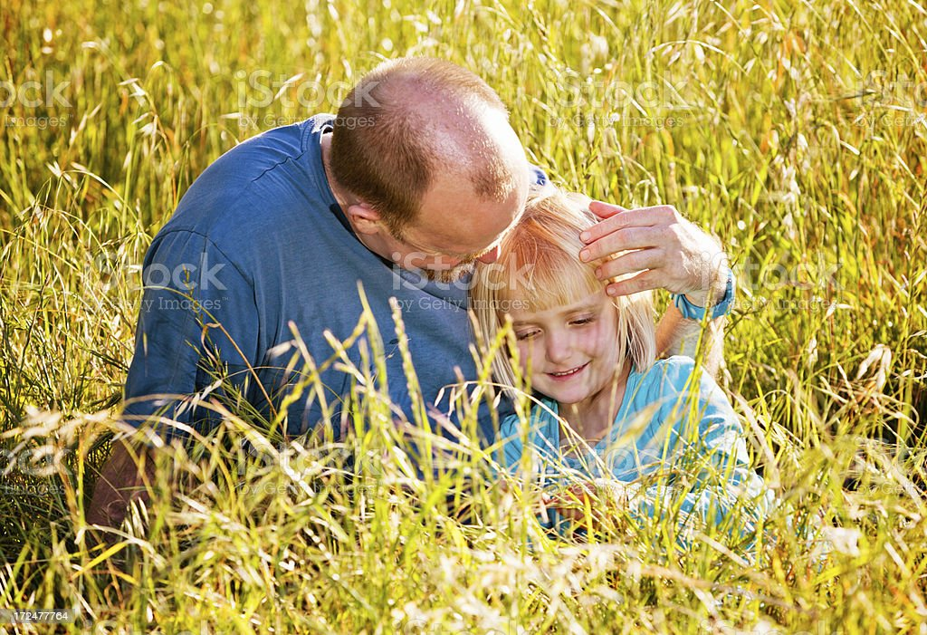 Happy families: father and daughter sitting in field stock photo