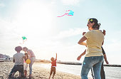 Happy families flying with kite and having fun on the beach - Parents playing with children outdoor - Love, and weekend holidays concept - Main focus on right woman face
