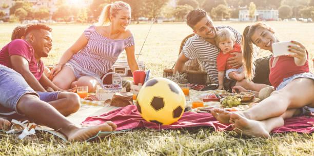 glückliche familien nehmen selfie und gemeinsam lachen bei picknick im stadtpark outdoor - eltern freunde spaß mit kindern am wochenendtag - sommer, trend und liebe technologiekonzept - gesichter im fokus - mensch isst gras stock-fotos und bilder