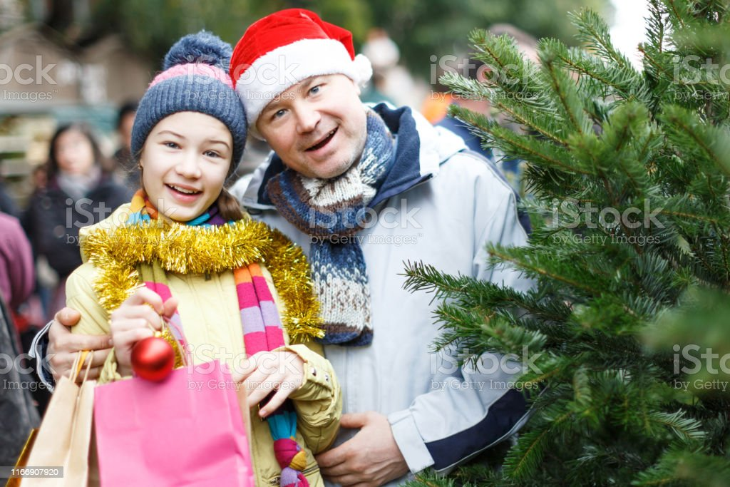Happy friendly family of father and teen daughter holding bags after...