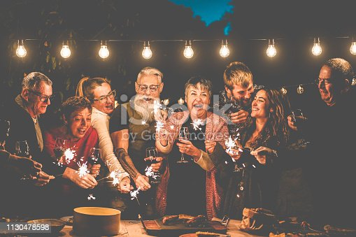 Happy family and friends celebrating with sparkler fireworks after dinner - Different age of people having fun drinking wine at birthday bbq party outdoor - Celebration concept - Focus on center faces