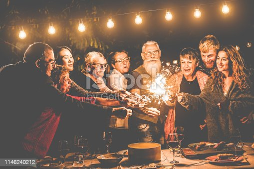 istock Happy family and friends celebrating with sparkler fireworks after dinner - Different age of people having fun at birthday bbq party outdoor - Celebration concept - Focus on left hands 1146240212