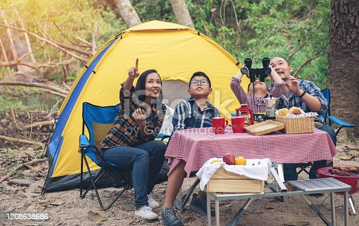 Happy Family Asian Enjoying holiday picnic and Camping and looking bird with binocular spyglass In Countryside. people travel outdoors concept.