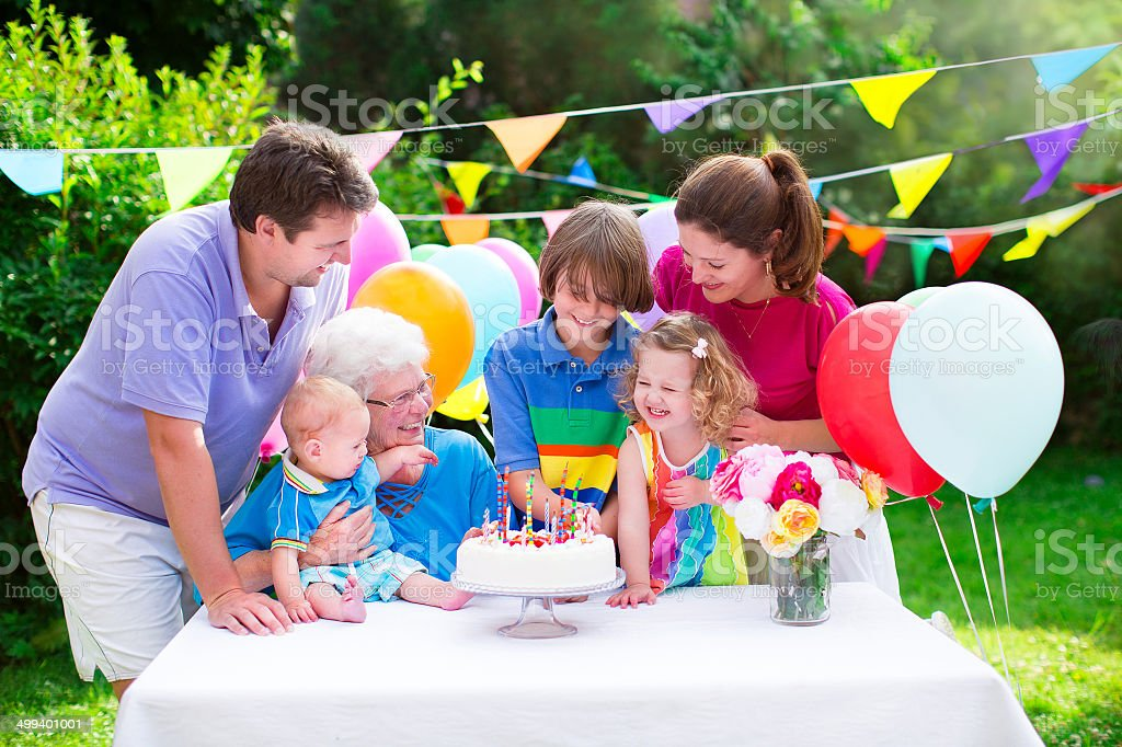 Happy family at a birthday party Happy big family - young parents, grandmother and three kids, teenage boy, toddler girl and little baby celebrating birthday party with cake and candles in the garden decorated with balloons and banners Adult Stock Photo