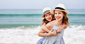 A young mother plays with her daughter girl of 3-4 years, on beach in summer, an outdoor resort by the lake. Happy rest on the weekend. Bright swimsuit on child. Parents love family and parenting.