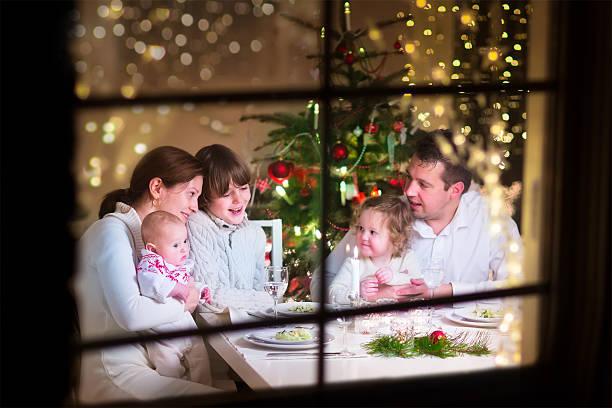 glückliche familie an weihnachten abendessen - kinderzimmer tischleuchten stock-fotos und bilder