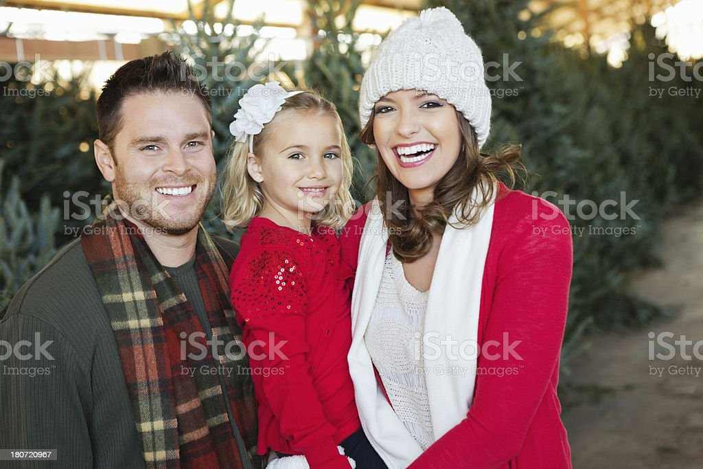 Happy family at Christmas tree farm on cold winter day royalty-free stock photo