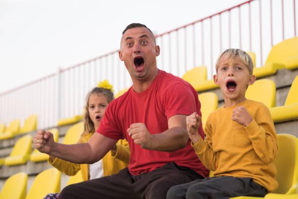 happy family im fußballstadion - jubeln stock-fotos und bilder
