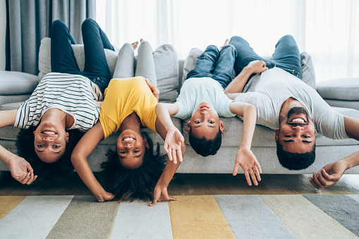 Shot of a cheerful family hanging upside down on the sofa at home.