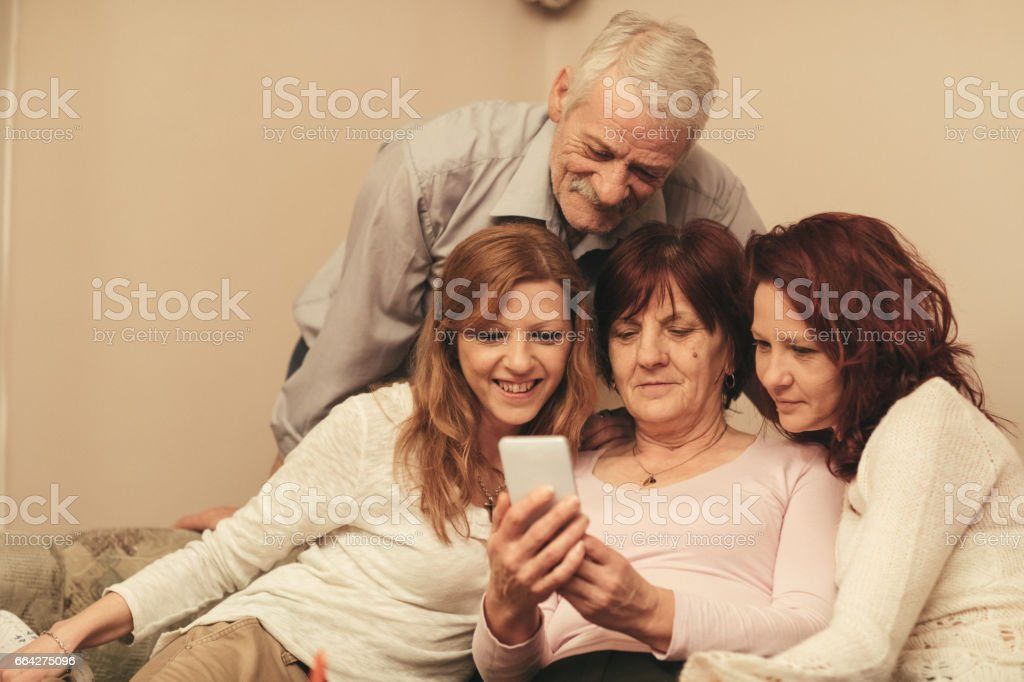 Happy family at home using mobile phone stock photo
