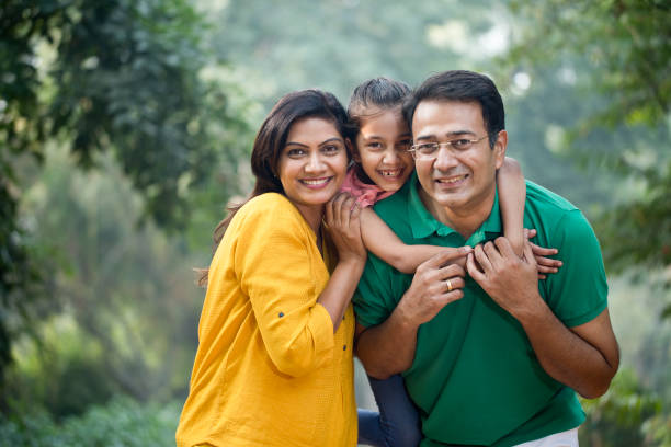 Happy family at park Father carrying daughter on shoulders at park indian family stock pictures, royalty-free photos & images