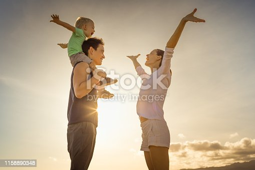 588959064istockphoto Happy family at sunset 1158890348