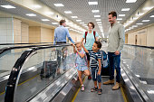 Happy family at the airport traveling and standing on a moving walkaway