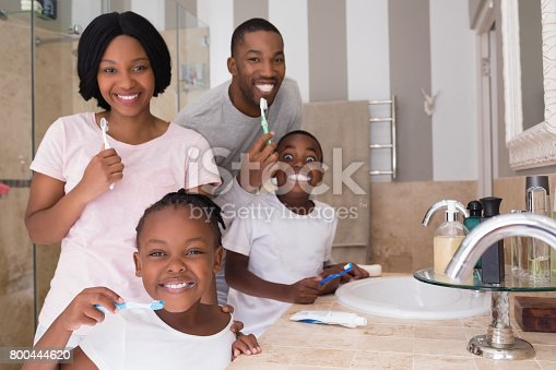 istock Happy family brushing teeth in bathroom at home 800444620