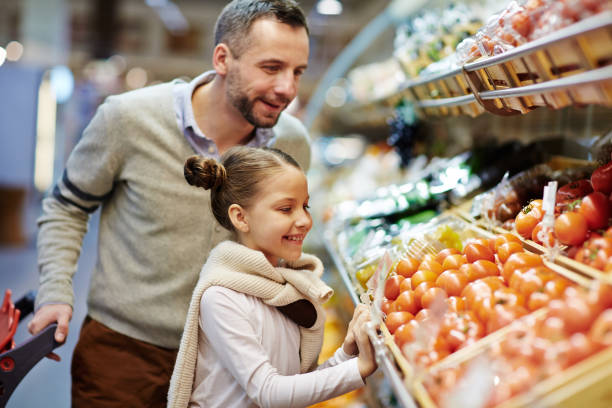 Happy Family Buying Fresh Vegetables stock photo