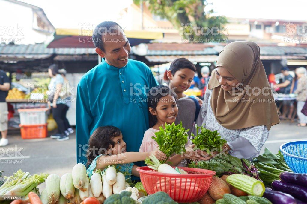 Lycklig familj att köpa bladgrönsak på stall - Royaltyfri 10-11 år Bildbanksbilder