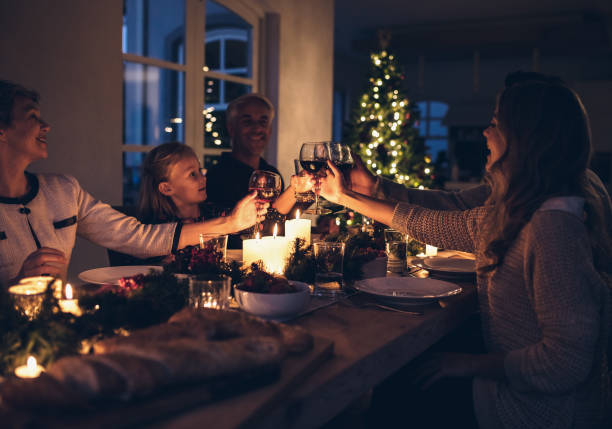 happy family celebrating christmas together at home - family dinner stock photos and pictures