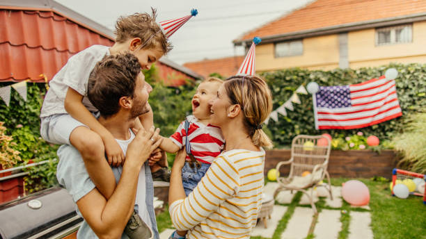 Happy family celebrating Fourth of July Photo of a happy family celebrating Fourth of July in their yard family 4th of july stock pictures, royalty-free photos & images