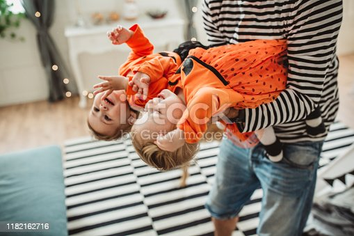 Cheerful Father With daughters celebrating Halloween At Home. They fooling around and wear costumes, father carrying them, home is decorated with flags