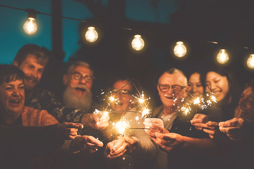 Happy family celebrating new year eve with sparkler outdoor - Group people with different ages and ethnicity having fun together in night party outside - Youth and elderly friendship lifestyle concept