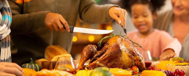 happy family celebrating thanksgiving dinner at home . celebration tradition concept - thanksgiving dinner zdjęcia i obrazy z banku zdjęć