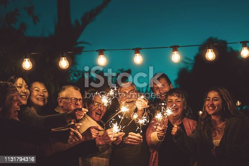 istock Happy family celebrating with sparkler at night party outdoor - Group of people with different ages and ethnicity having fun together outside - Friendship, eve and celebration concept 1131794316