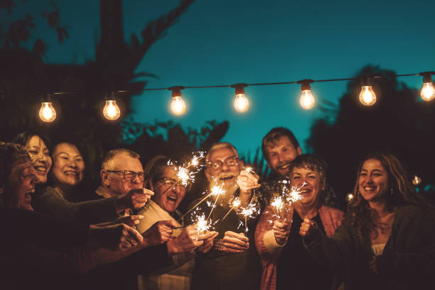 happy family celebrating with sparkler at night party outdoor - group of people with different ages and ethnicity having fun together outside - friendship, eve and celebration concept - party social event stock pictures, royalty-free photos & images