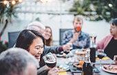 幸せな家族の歓声と食事一緒に屋外-バーベキューディナーパーティーで楽しいと異なる年齢と民族性を持つ人々-食べ物や飲み物、退職し、若い人の概念