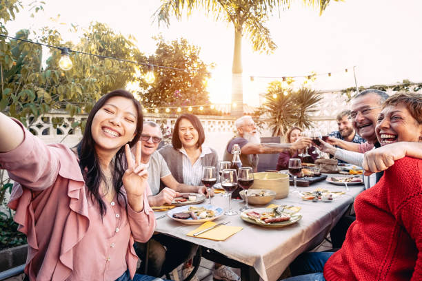 happy family cheering and toasting with red wine glasses at dinner outdoor - people with different ages and ethnicity  having fun at bbq party - food and drink, retired and young people concept - kolacja spotkanie towarzyskie zdjęcia i obrazy z banku zdjęć