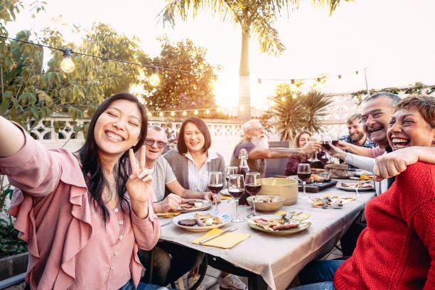 happy family juichen en toasten met rode wijnglazen bij het diner buiten-mensen met verschillende leeftijden en etniciteit plezier op bbq party-eten en drinken, gepensioneerden en jonge mensen concept - barbecue maaltijd stockfoto's en -beelden