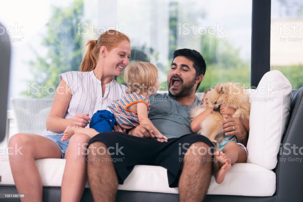 Happy family cheering while siting on sofa at home. stock photo