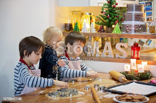 istock Happy family, children, preparing dough for cookies and baking gingerbread cookies for Christmas 1076842146