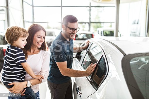 Young happy family enjoying while buying a new car in a showroom.