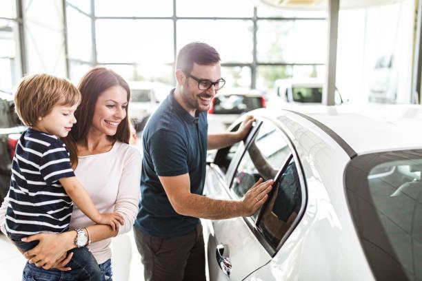 famiglia felice che sceglie un'auto nuova in uno showroom. - auto foto e immagini stock