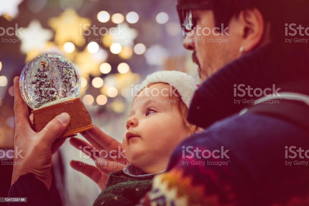 Happy family choosing snow globe in Christmas stock photo