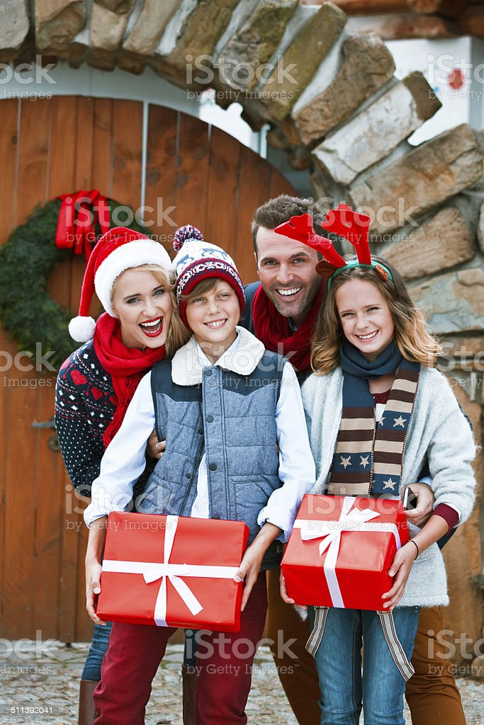Happy Family, Christmas Portrait Christmas portrait of happy family standing in front of doors decorated with christmas wreath. Children holding christmas gifts. 10-11 Years Stock Photo