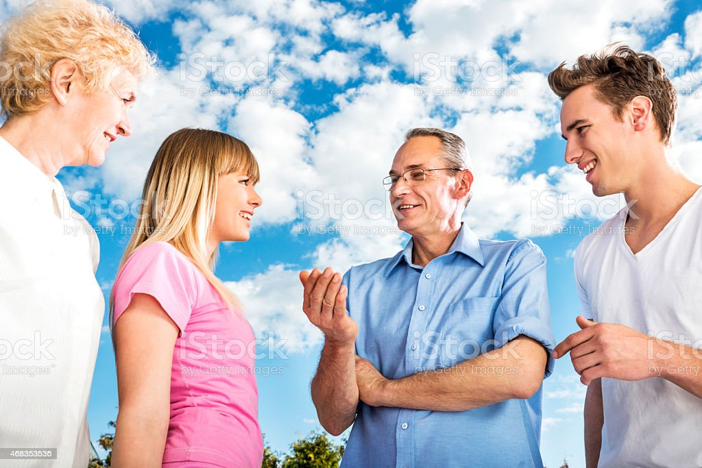 Happy family communicating against the sky. royalty-free stock photo