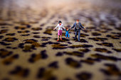 Happy Family Concept. present by Miniature Figure of Father, Mother and Son with Happiness Moment. Walking on Tiger Printed  Fabric