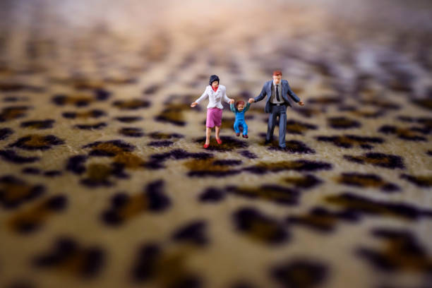 happy family concept. present by miniature figure of father, mother and son with happiness moment. walking on tiger printed  fabric - figurine stock photos and pictures