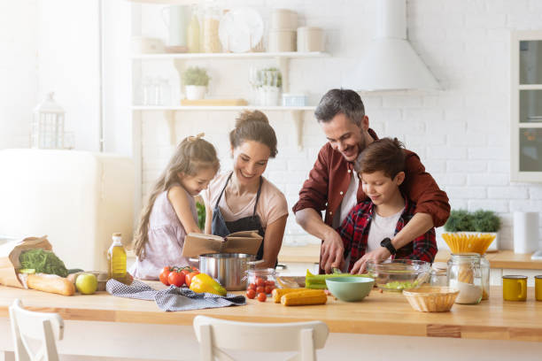 Happy family cooking together on home kitchen stock photo