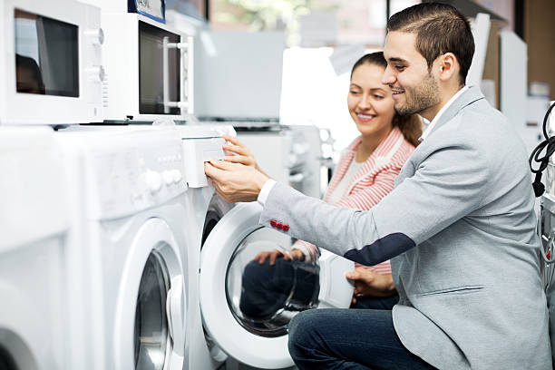 Happy family couple buying new clothes washer stock photo
