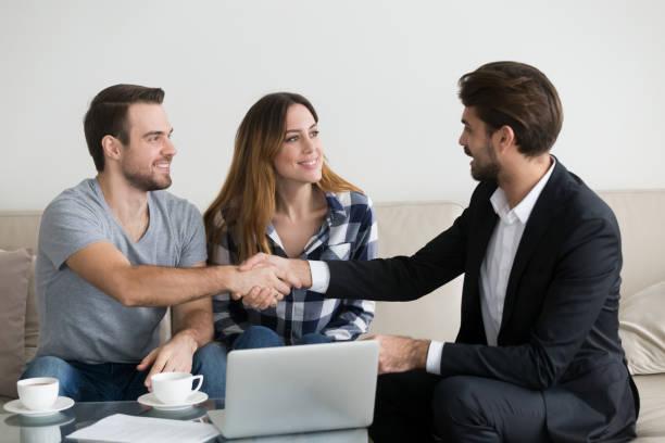 happy family couple renters tenants handshaking realtor landlord at meeting - locatario foto e immagini stock