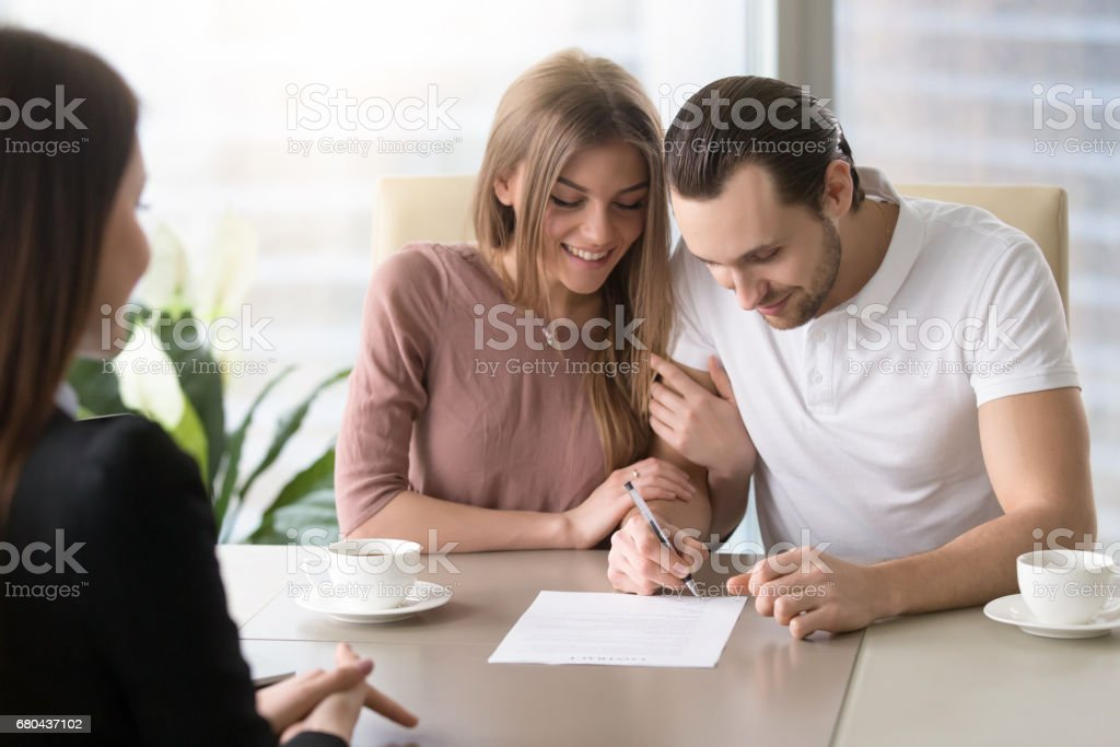 Happy family couple signing document, taking out bank loan, insurance stock photo