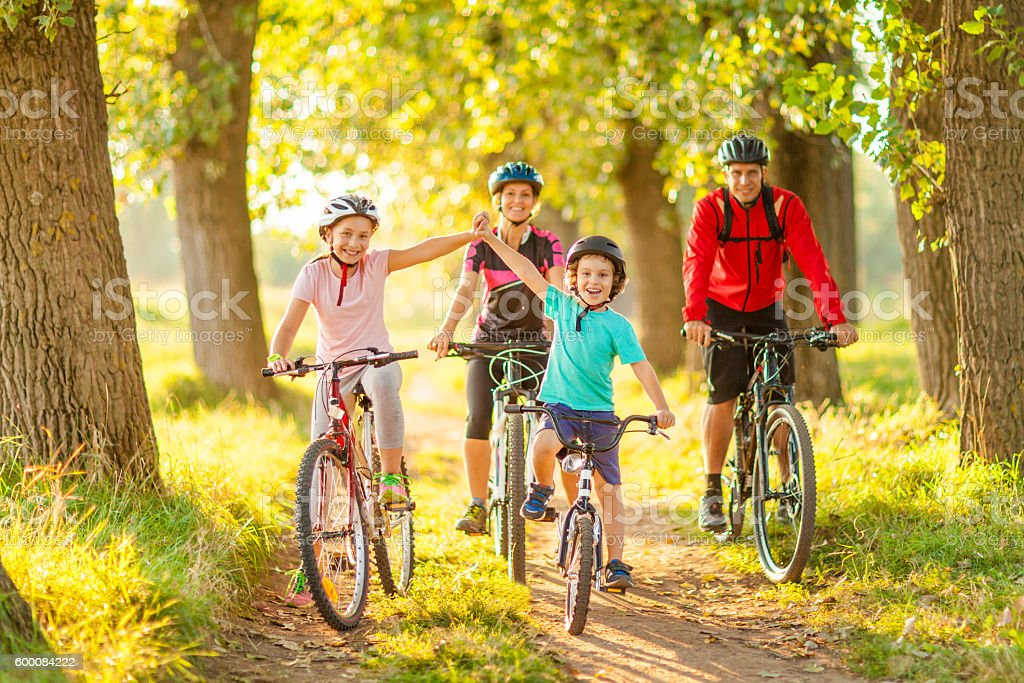 Happy family cycling in the countryside - foto de acervo