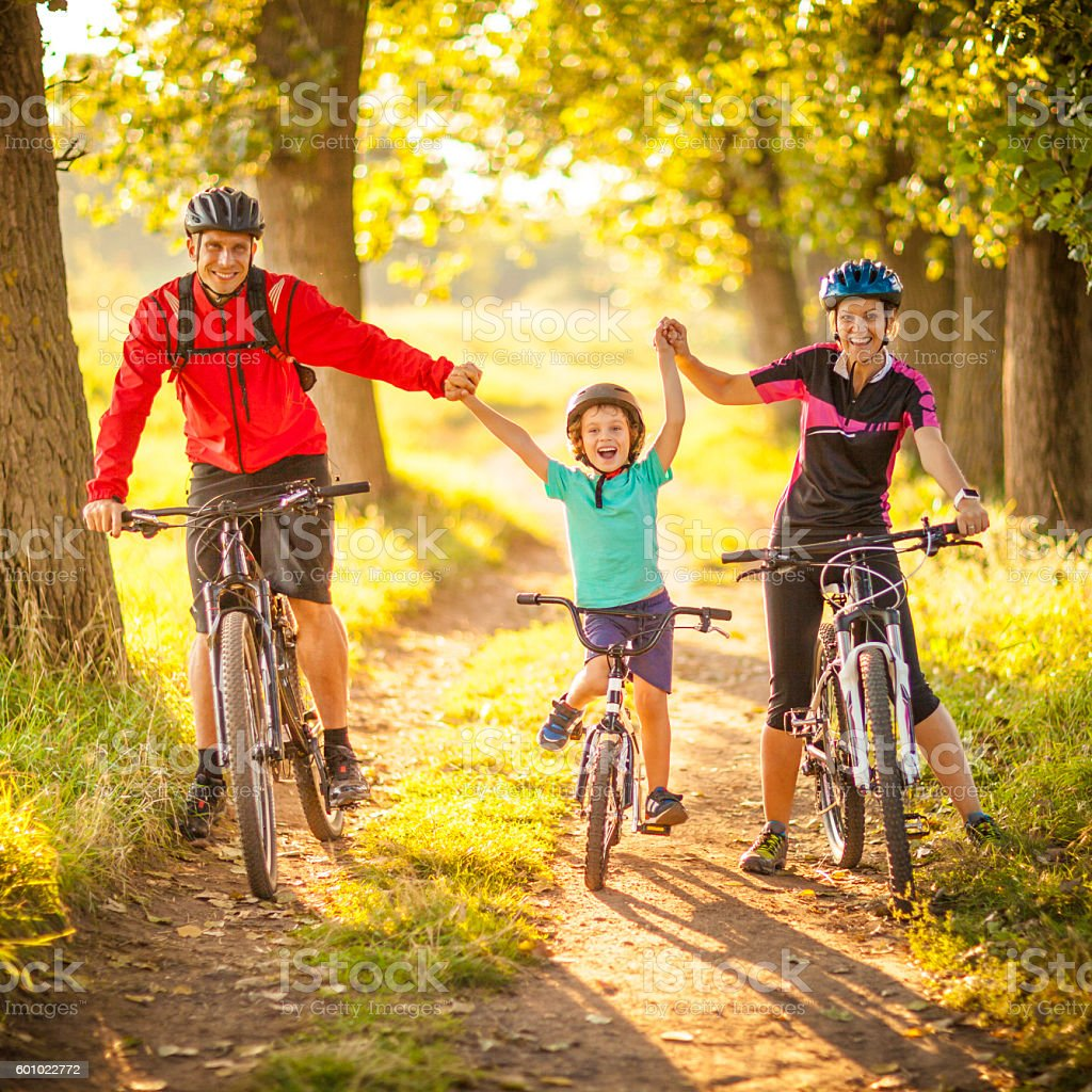 Happy family cycling in the countryside stock photo