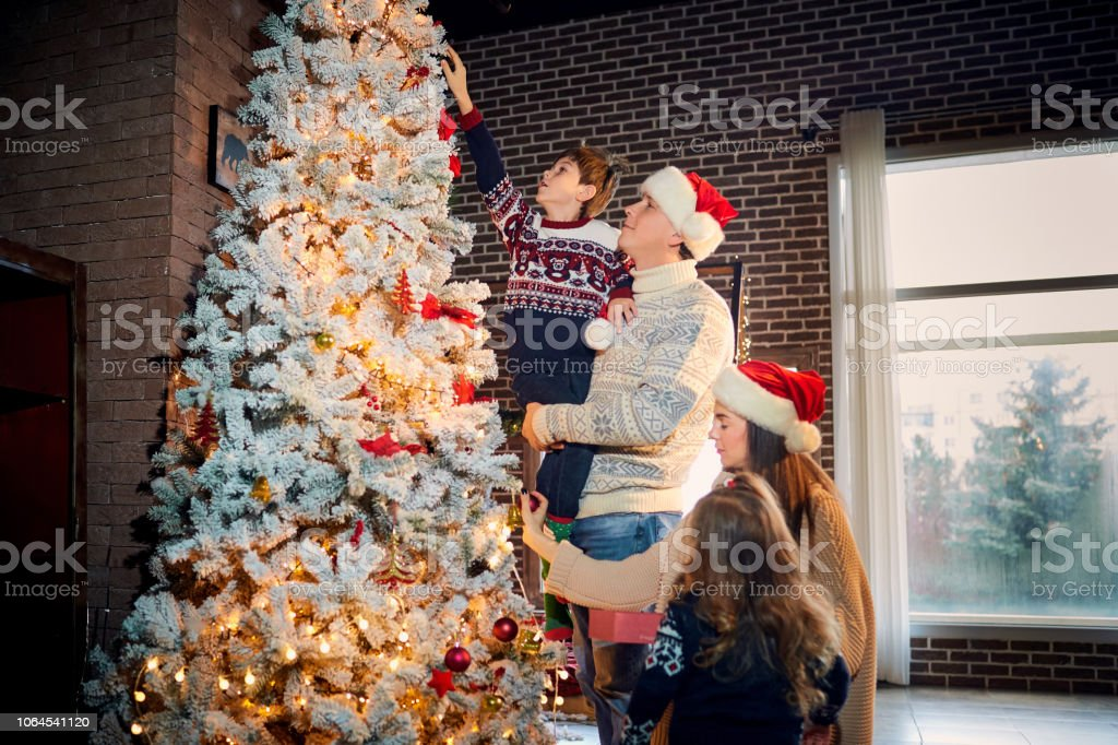 A happy family decorates a Christmas tree at home on Christmas Day.